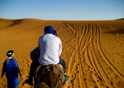 Camel driver leading the way on a private guided Sahara Desert trek with Experience Morocco