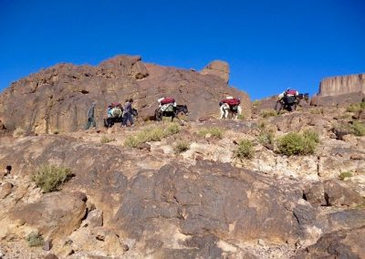 Hiking over volcanic rock on a private guide hike in Jebel Saghro mountain range with Experience Morocco