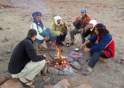 Sitting around the campfire on a guided hike in Jebel Saghro mountain range with Experience Morocco