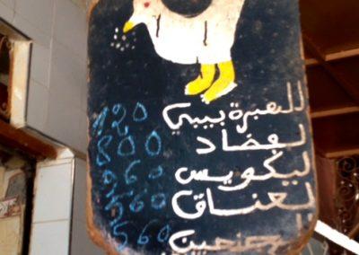 Sign for live chicken seller in Marrakech souk